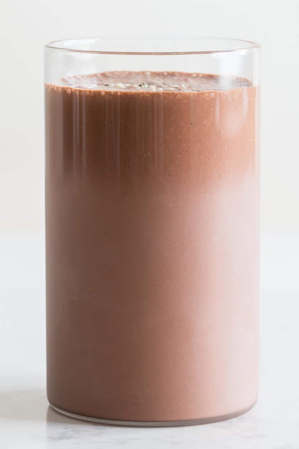 A glass full of vegan Chocolate Peanut Butter Banana Smoothie.