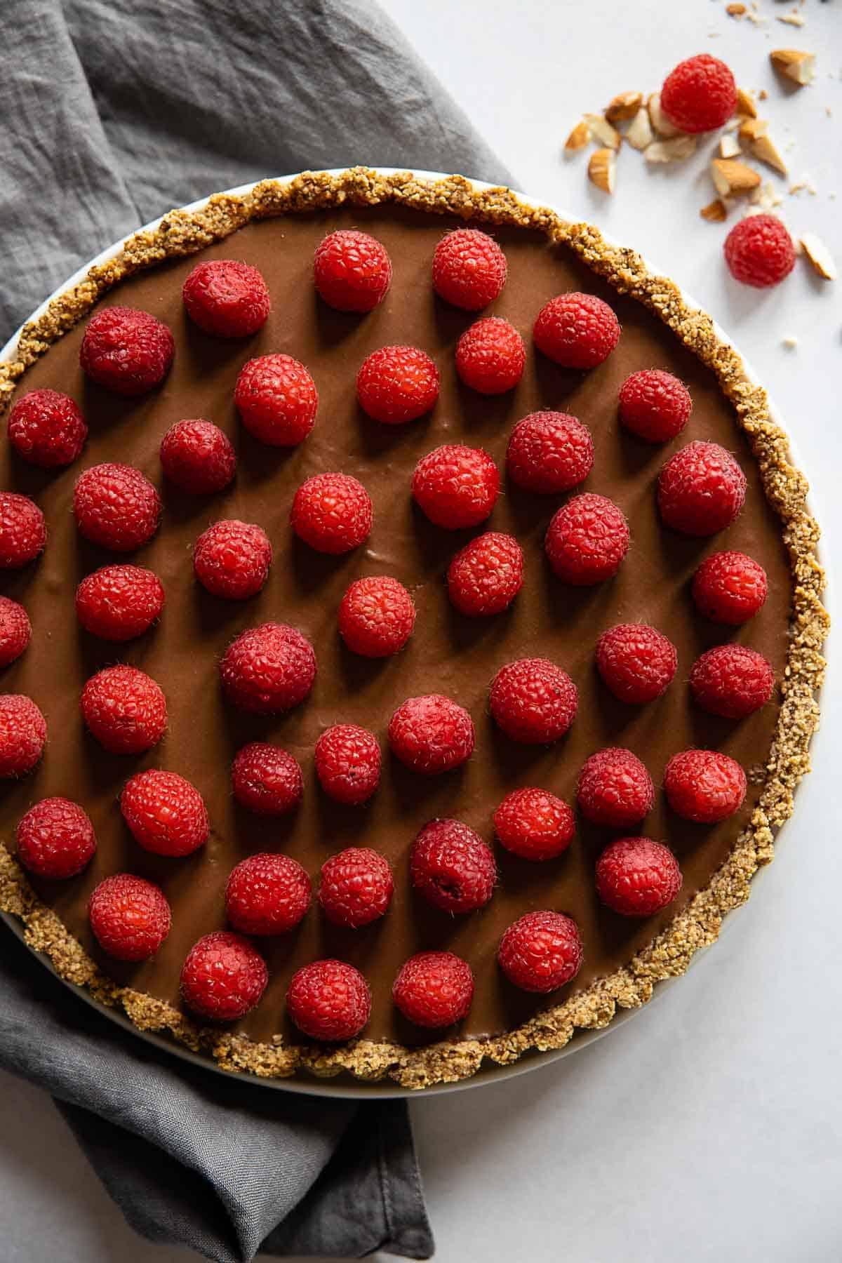 Chocolate Raspberry Tart with grey napkin next to it.