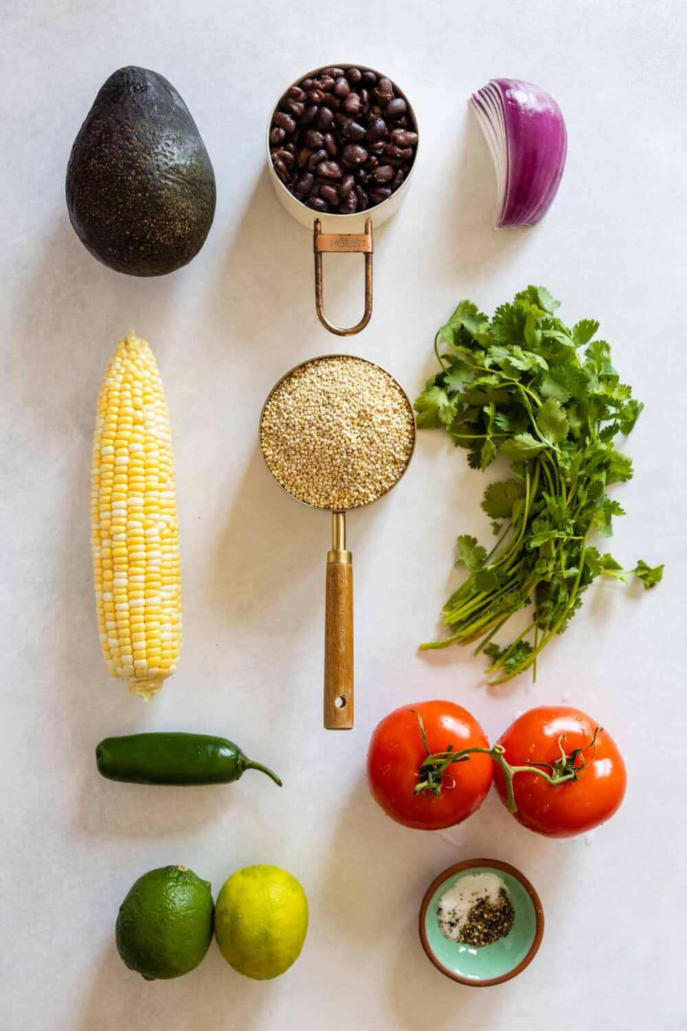All ingredients for Mexican Quinoa Salad laid out on a kitchen counter.