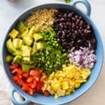 Mexican Quinoa Salad ingredients shown separately in a blue bowl before mixing.