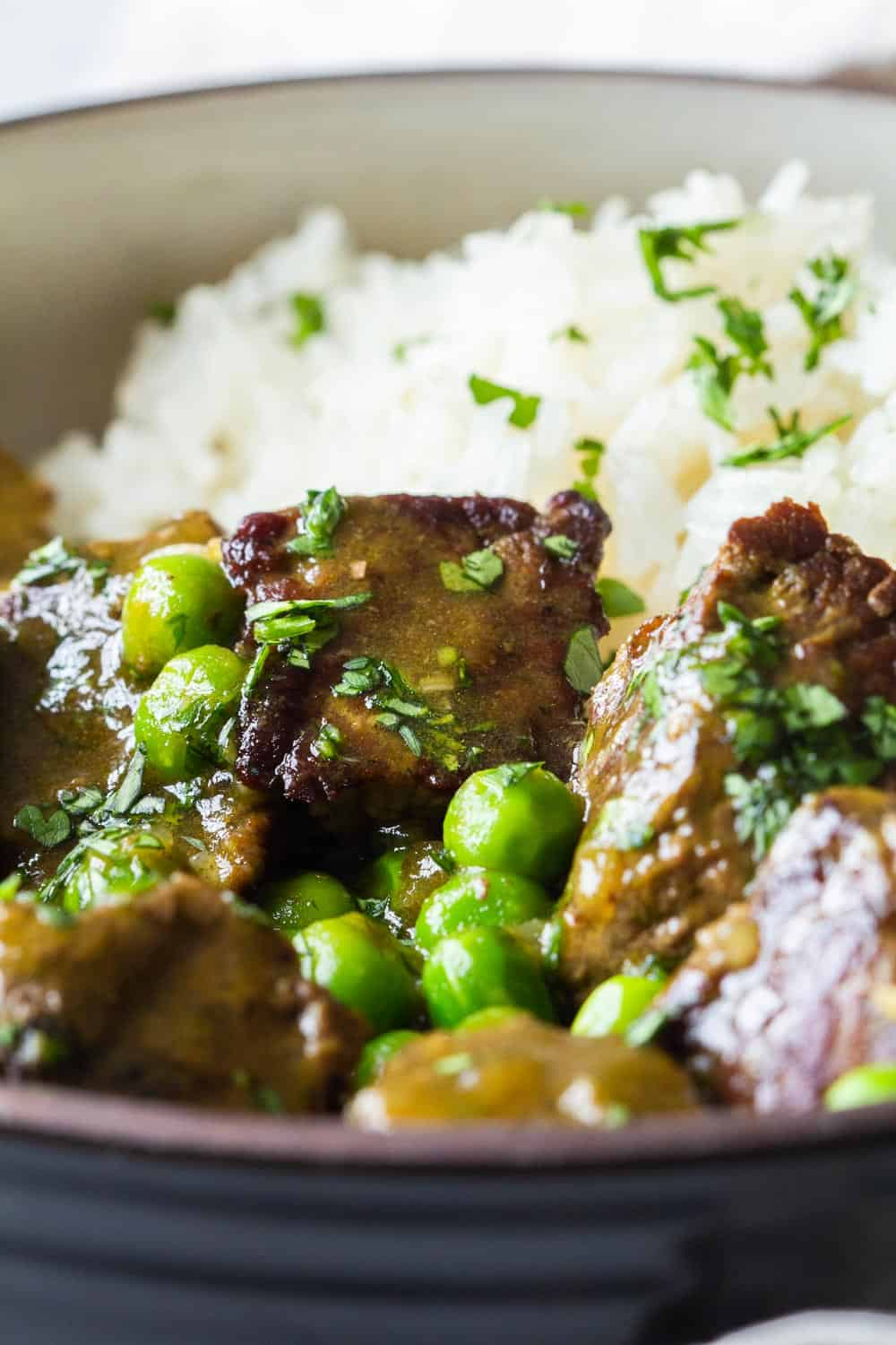 Close-up of texture of Instant Pot Beef Stew with peas and white rice