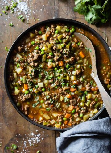 Mexican Picadillo in a large pan on a wooden table.