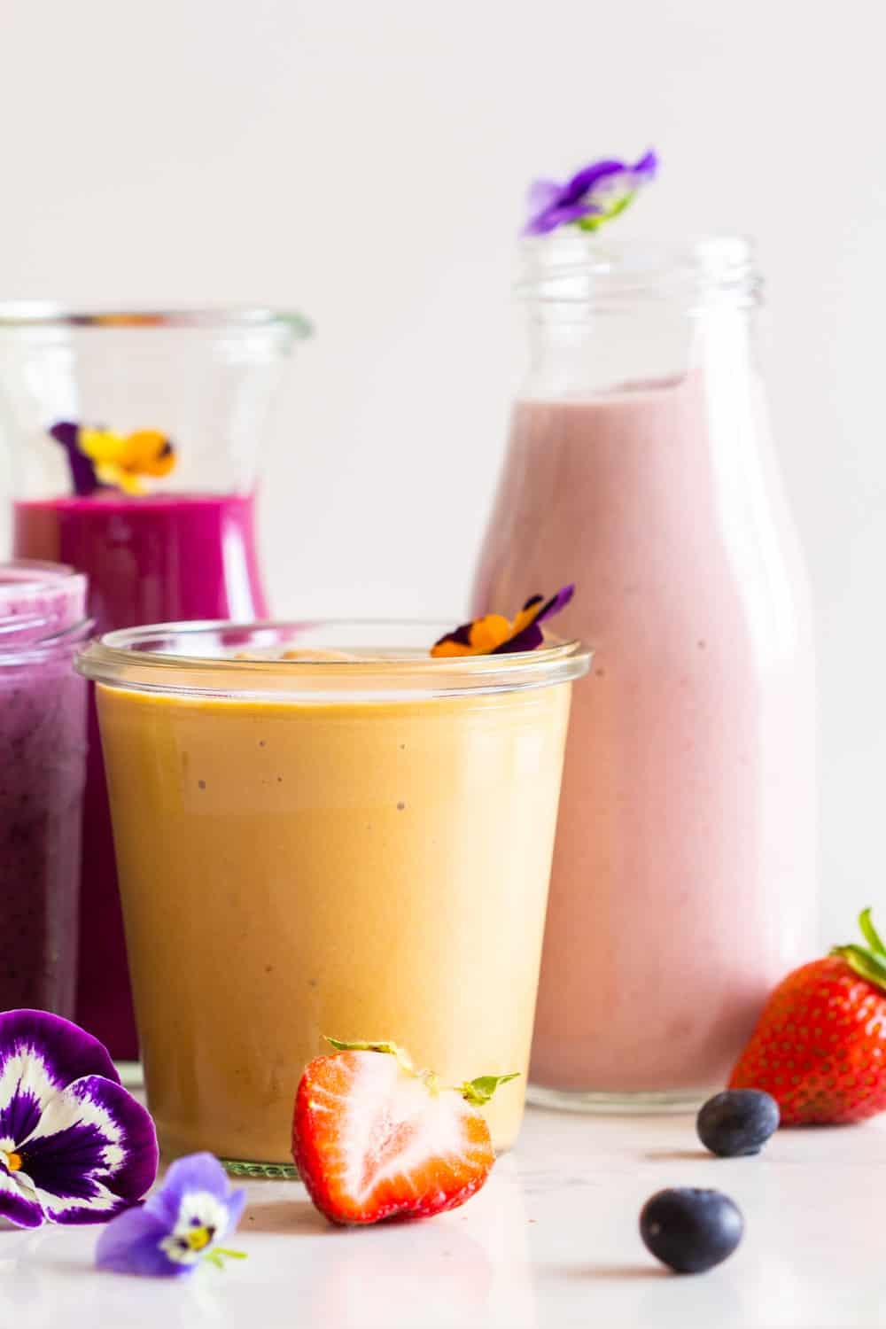 Healthy Breakfast Smoothie Recipes made with different colored fruits and vegetables in glass jars.