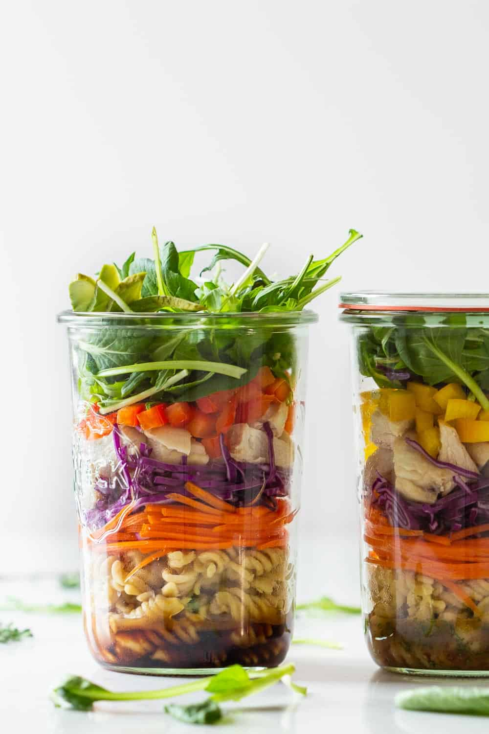 Pasta Salad with Chicken in two jars filled in layers. One dark dressing, one light dressing.