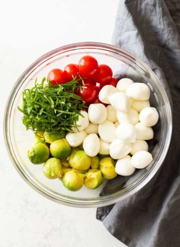 Ingredients for Avocado Tomato Salad in a glass bowl