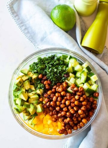 Cucumber Avocado Salad with crispy spicy chickpeas in a glass bowl next to a pale blue napkin