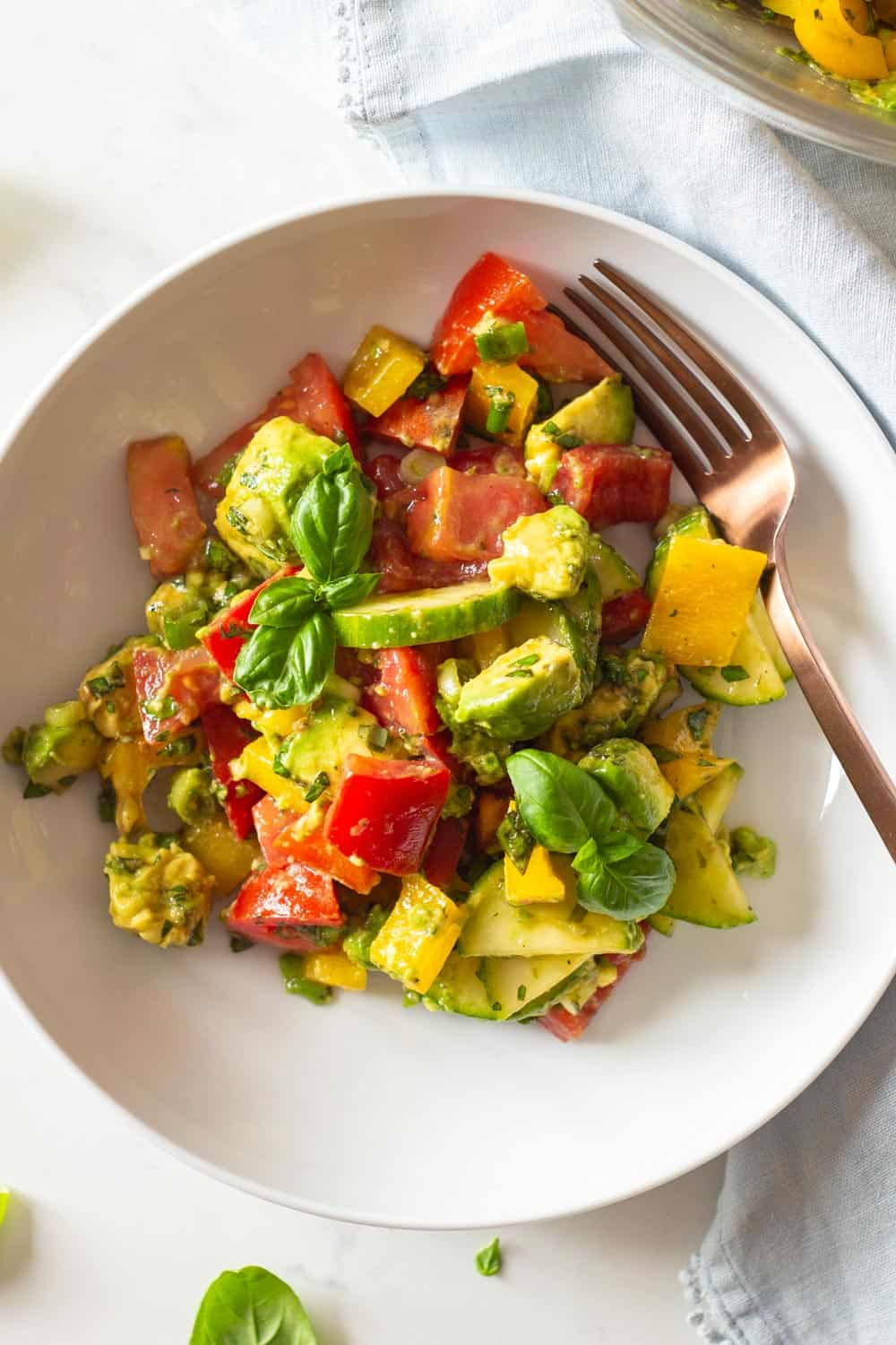 Tomato Cucumber Avocado Salad mixed up and served in a white salad bowl
