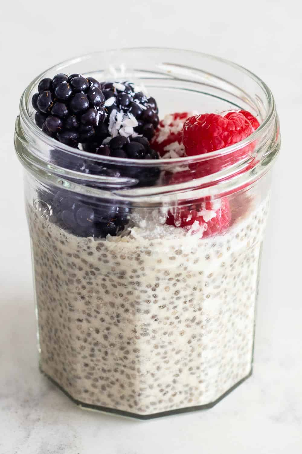 Coconut milk Chia Seed Pudding in a glass jar topped with blackberries and raspberries.