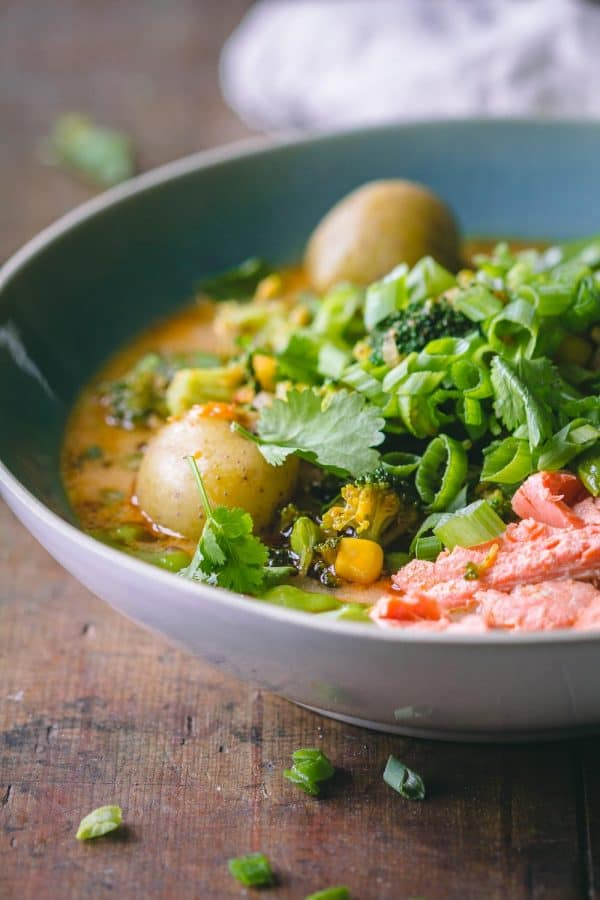 Thai Curry Soup in a blue bowl showing shredded salmon, potatoes, broccoli, and snow peas in broth