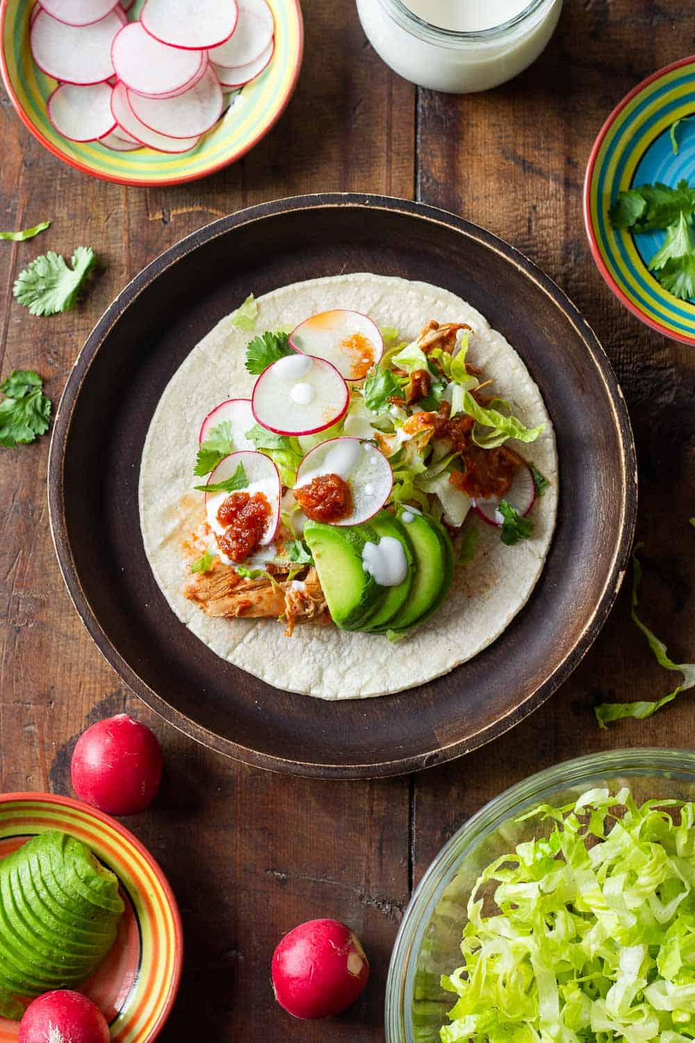Crockpot Chicken Tacos topped with lettuce, radish, sour cream and avocado