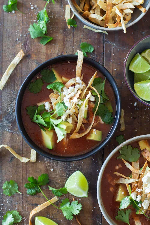 Crock Pot Chicken Tortilla Soup topped with crispy tortilla strips, avocado, cilantro and queso fresco
