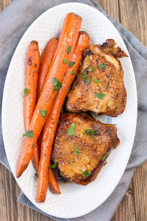 slow cooker balsamic chicken thighs and carrots on white platter