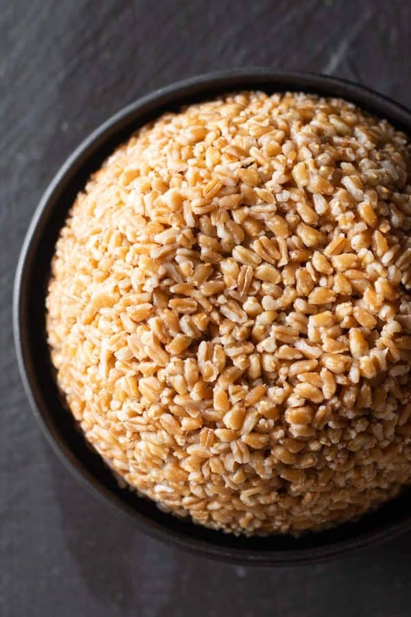 cooked farro in a black bowl