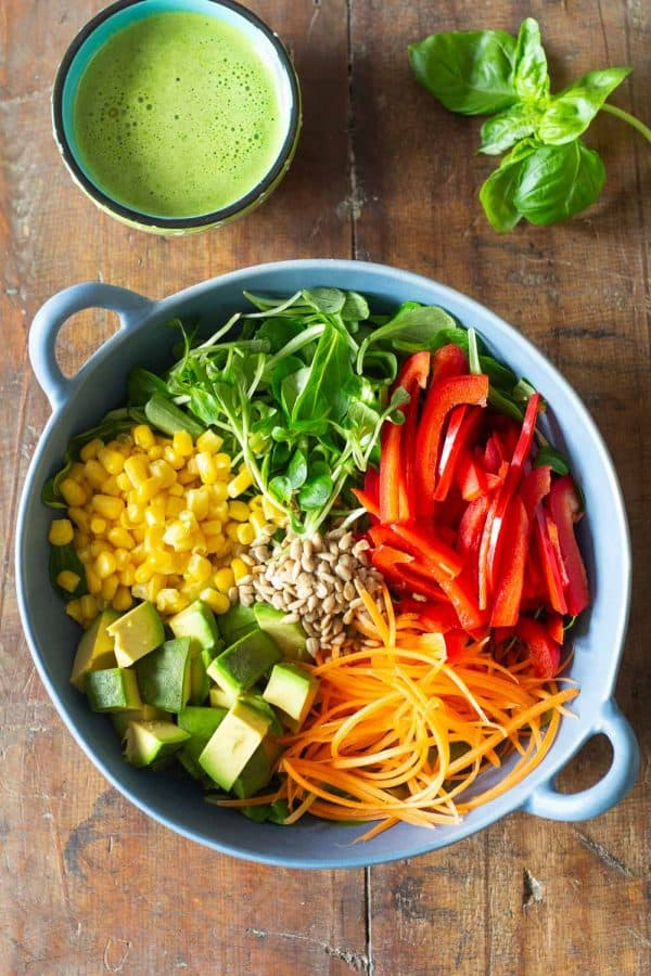 Ingredients for healthy summer salad with fresh vegetables in a light blue salad bowl, and a cup of orange basil vinaigrette.
