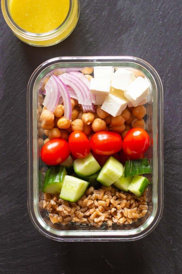 vegetarian meal prep bowl containing farro, cucumber, grape tomatoes, chickpeas, farro, red onion, and lemon tahini dressing