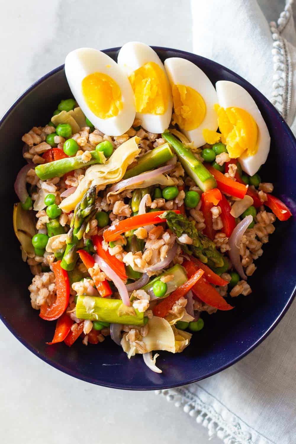 Farro Spring Salad in a bowl with hard boiled eggs on top