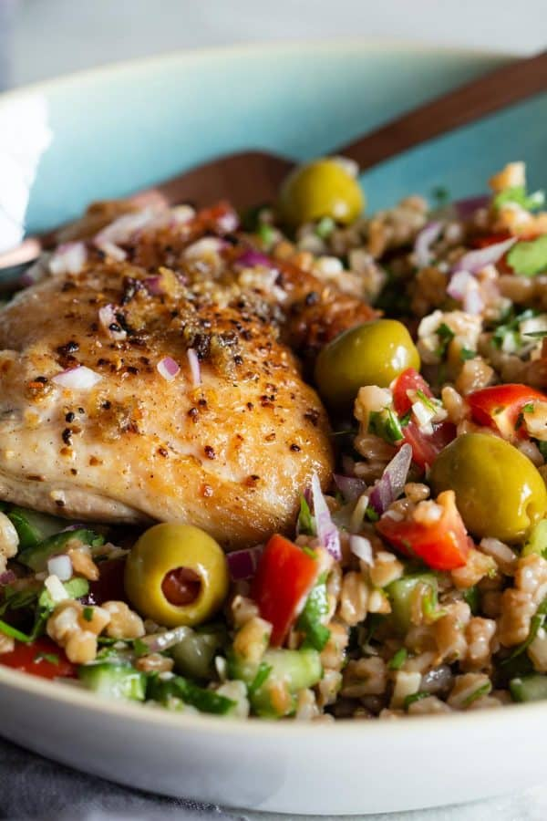 Mediterranean farro salad topped with a pan-seared chicken thigh