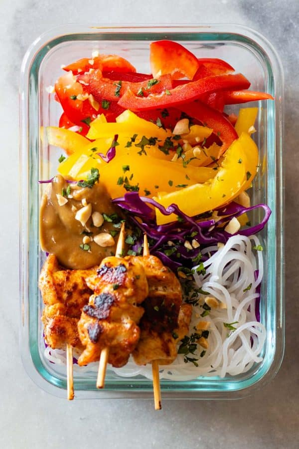 Chicken Satay on wooden skewers with raw vegetables served on rice noodles with peanut sauce