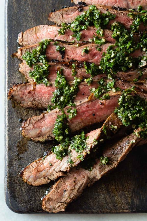 Sliced Flank Steak with Chimichurri on a cutting board