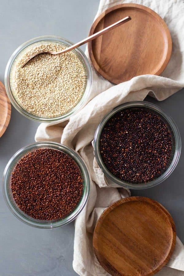 Raw white quinoa, raw red quinoa, and raw black quinoa in jars