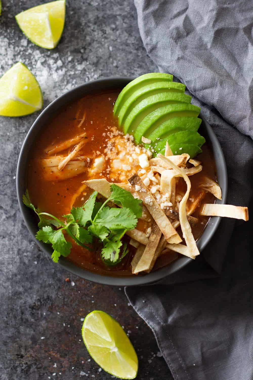 Instant Pot Chicken Tortilla Soup in a black bowl topped with avocado tortilla strips and cilantro