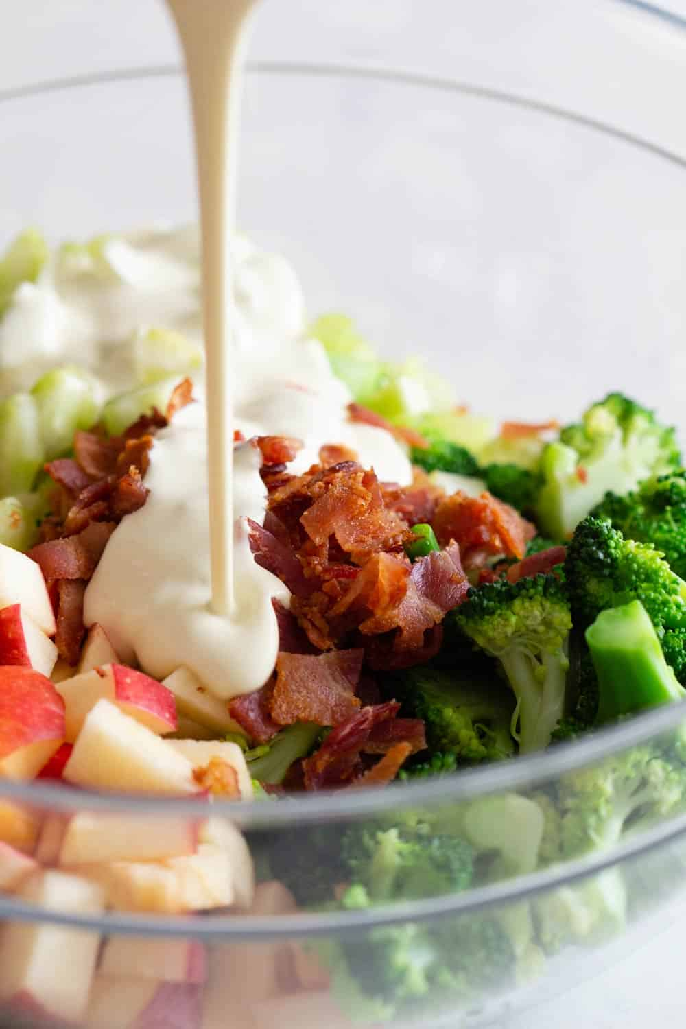 Broccoli Salad in a bowl and dressing poured in