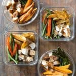 4 meal prep containers with cubed chicken, sweet potato wedges, potato wedges, asparagus, green beans, and bell pepper.