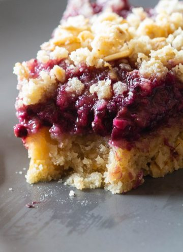 One piece of a Blackberry Pie with crumbles on top.