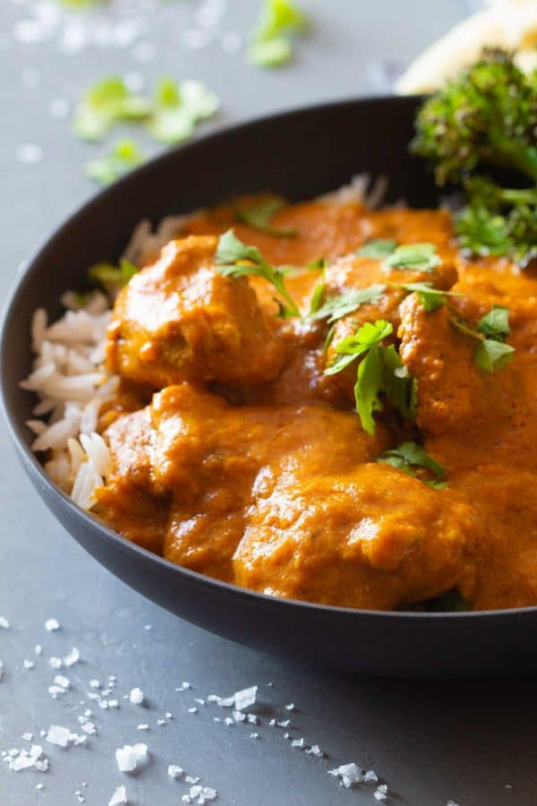Close-up shot of texture of butter chicken in a grey bowl topped with parsley