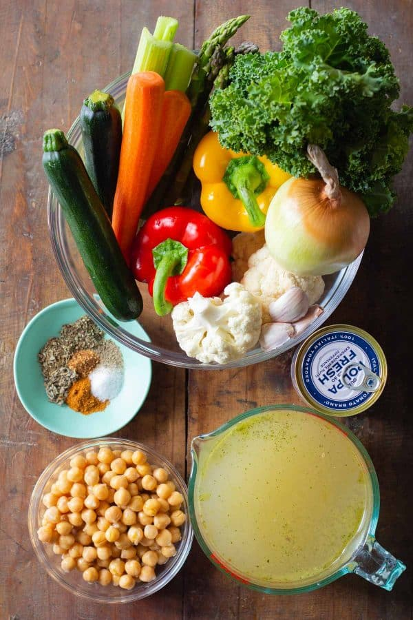 Ingredients for Vegetable Soup in bowls on a wooden table