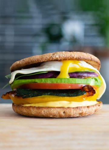 multi-layered sandwich with different colored vegetables and a fried egg on top on a cutting board