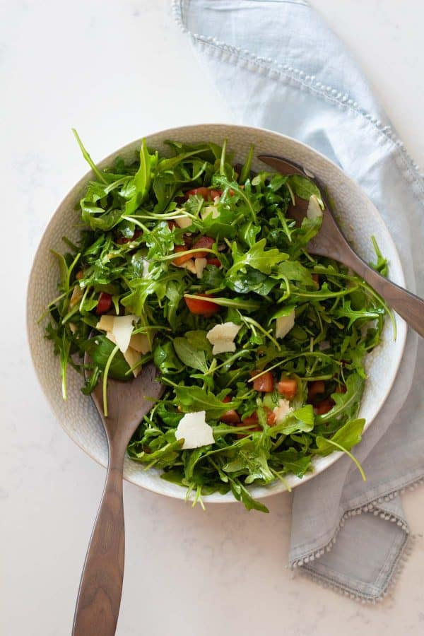 A mixed arugula salad in a white bowl