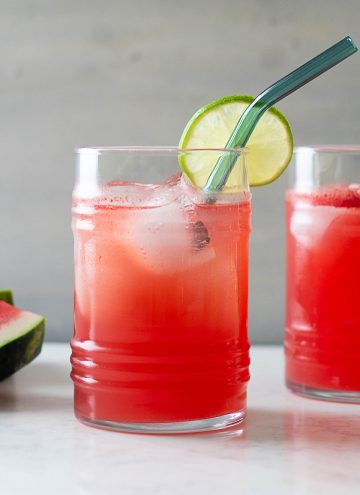 watermelon agua fresca in a glass with lime slice at edge and blue glass straw