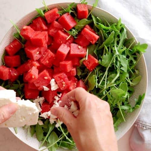crumbleing feta cheese into salad bowl