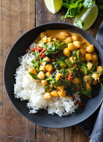 Bowl with white rice and coconut chickpea curry with baby spinach.