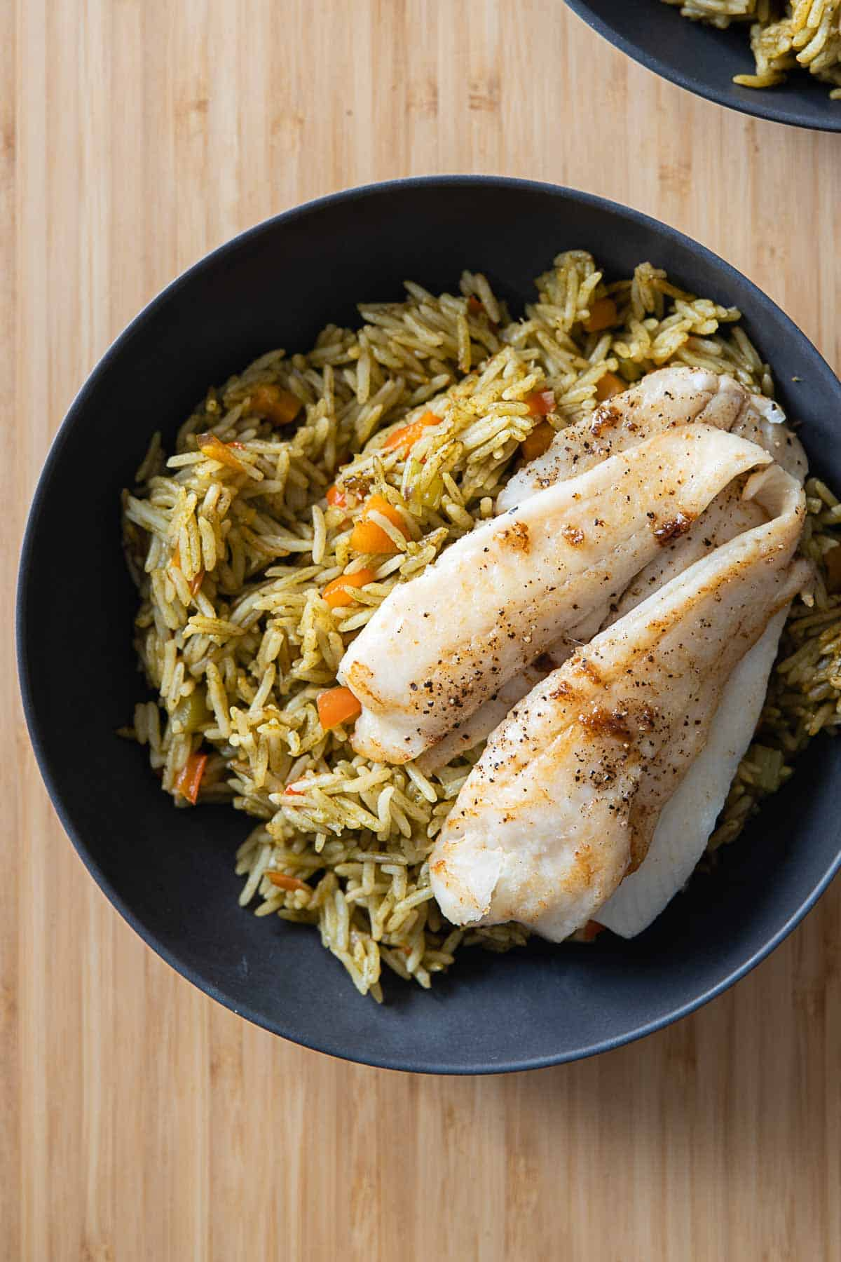 Green Rice and sole fillet in a grey bowl.