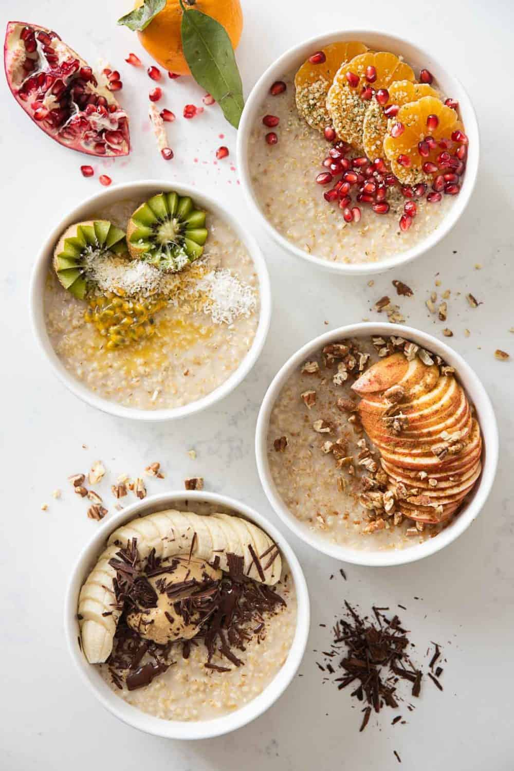 4 bowls of creamy steel cut oats topped with fall/winter fruit, nuts, and seeds.
