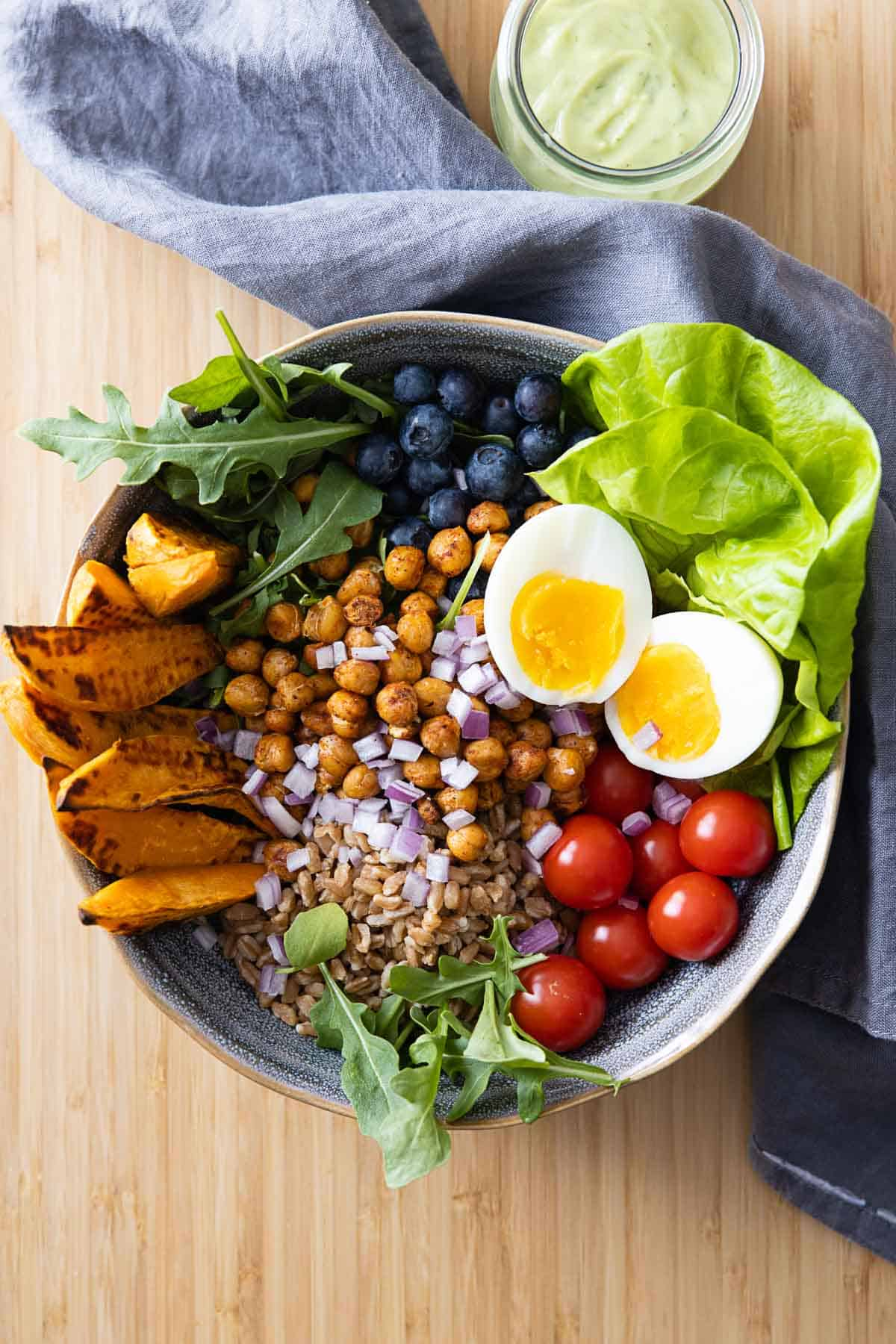 Bowl filled with lettuce, roasted sweet potato, roasted chickpeas, tomatoes, farro, red onion, blueberries, and a hard-boiled egg.