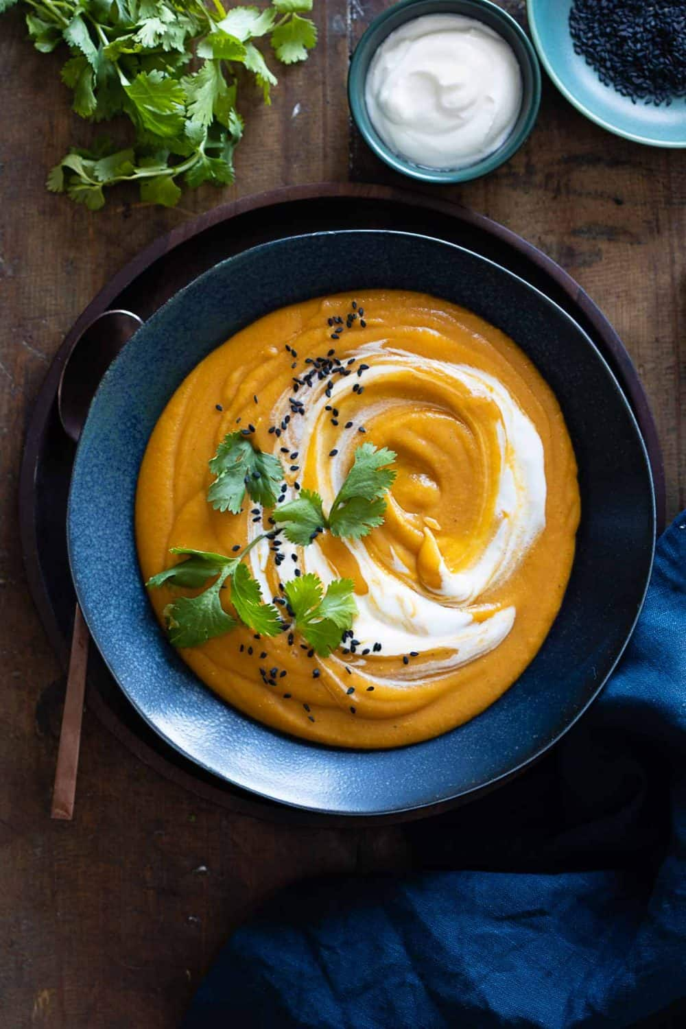 Red Lentil Sweet Potato Soup in blue bowl with swirl of sour cream.