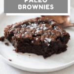 Closeup of a brownie piece on a white plate to show texture on the inside. paleo brownies recipe with text overlay for Pinterest.