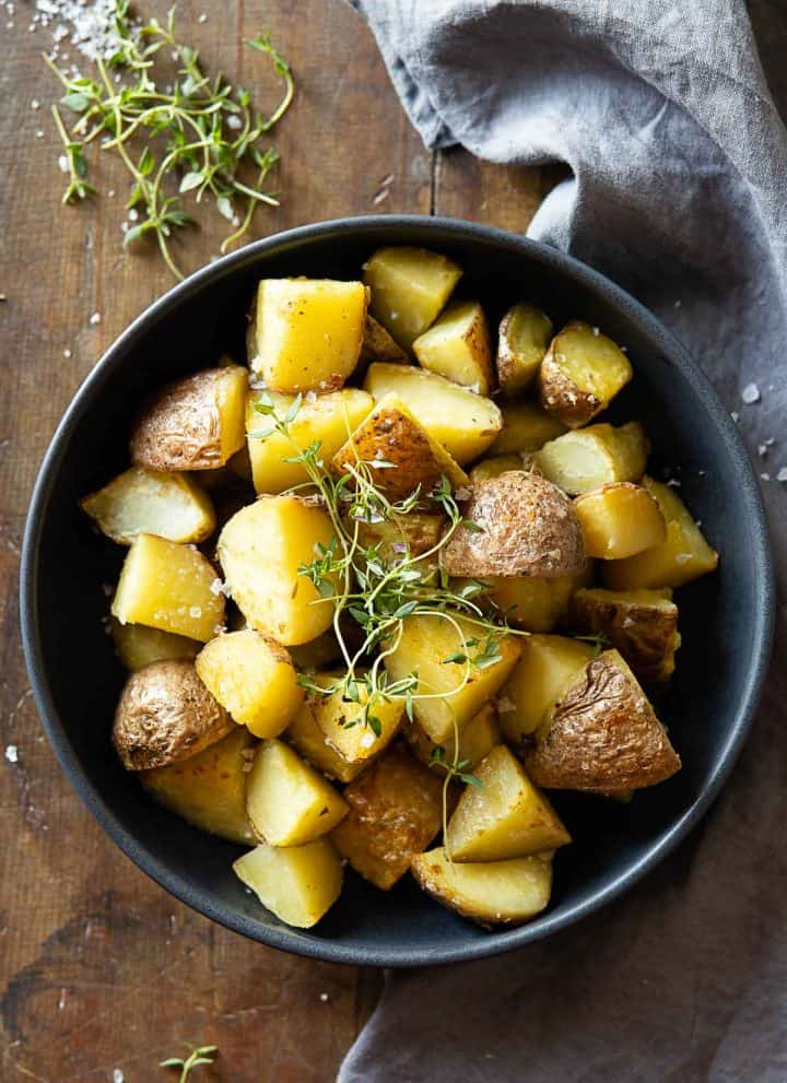 Cooked cut up red potatoes in a grey bowl garnished with fresh thyme.