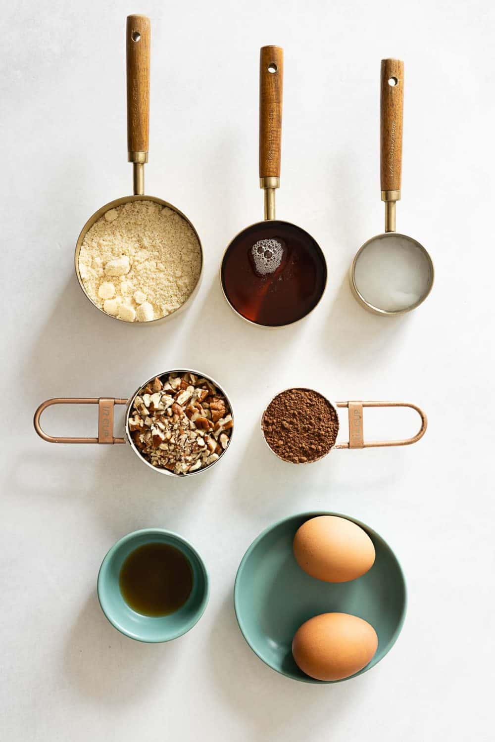 7 Brownie Ingredients in measuring cups on a kitchen counter.