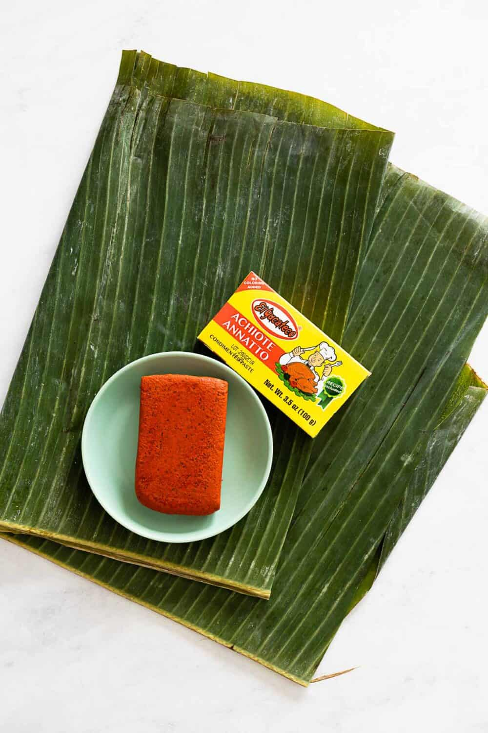 A folded banana leaf and a block of achiote paste.