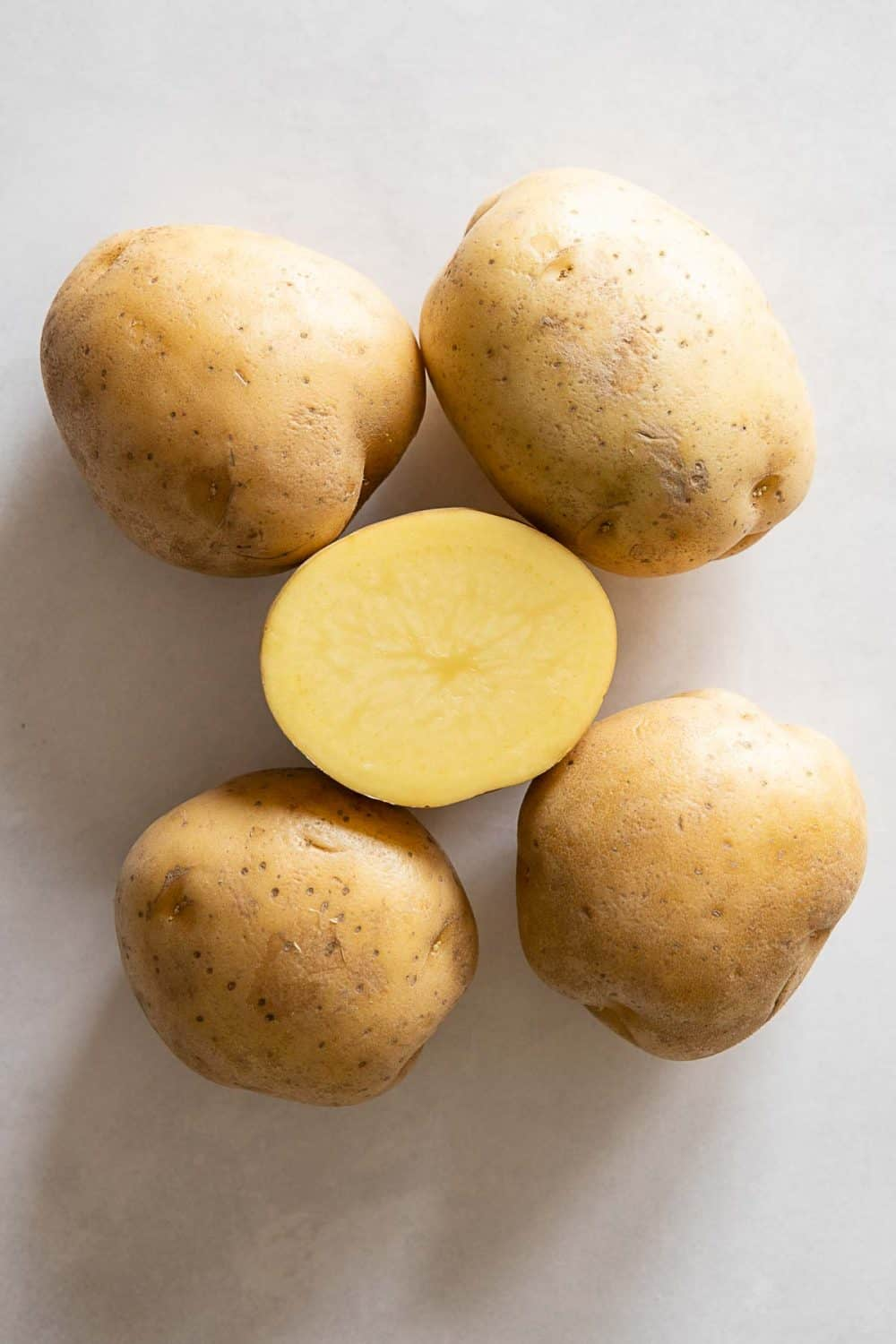 5 Yellow-fleshed potatoes, one cut open to show color. Instant Pot Mashed Potatoes recipe