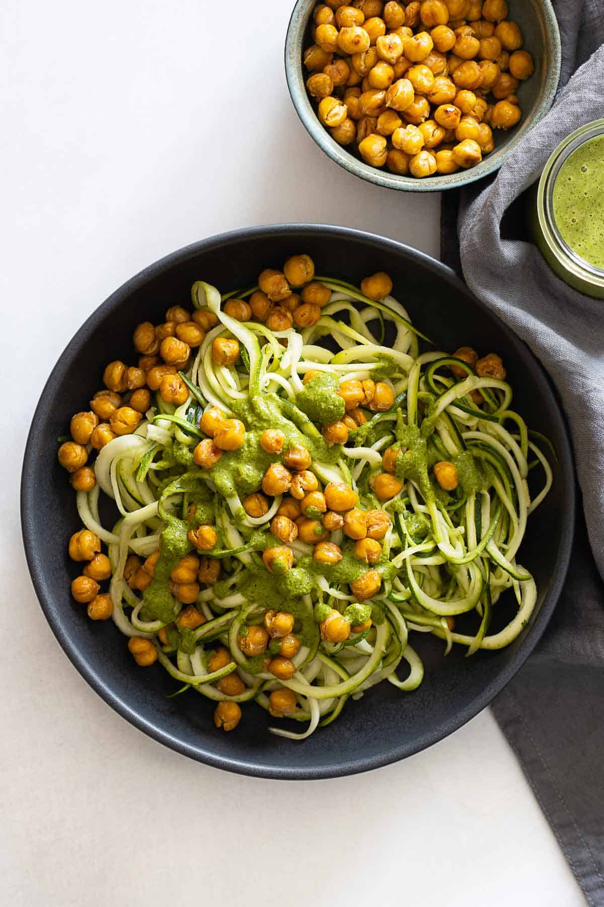 Zucchini noodles topped with crispy chickpeas and herb sauce.