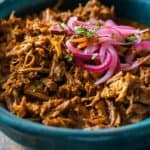 Closeup look of texture of Cochinita Pibil served in a blue bowl and topped with red onion.