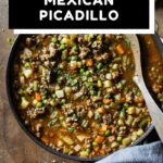 Mexican Picadillo in a large pan on a wooden table with text overlay for Pinterest.