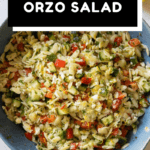 Lemon Orzo Salad in a blue bowl shown from the top down with text overlay for Pinterest.