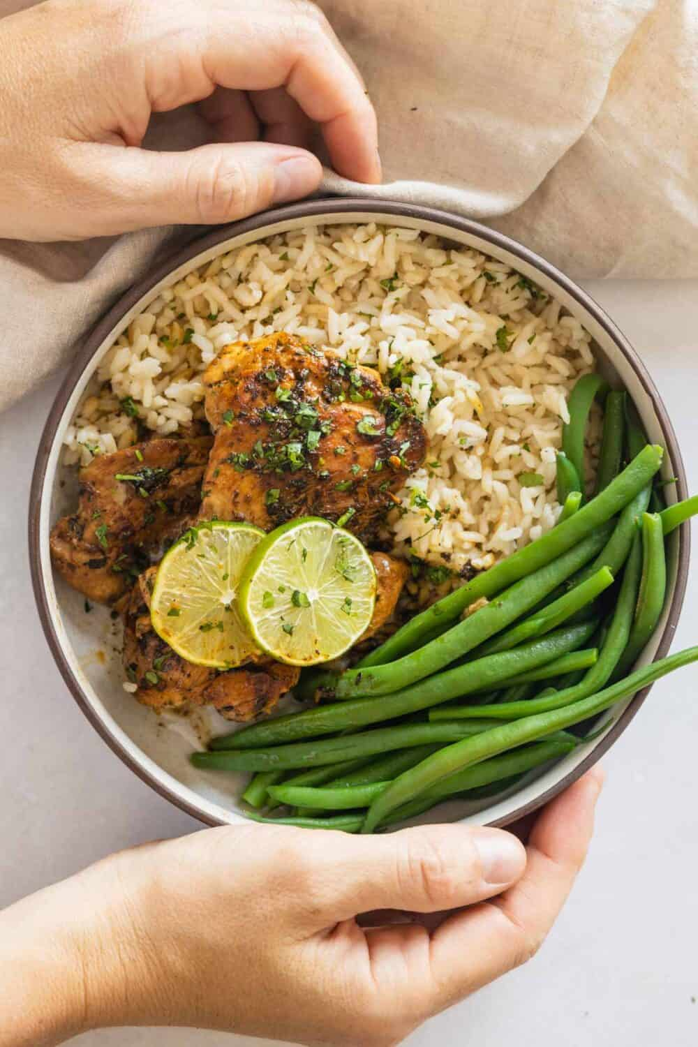 Coconut rice, cilantro lime chicken thighs, and green beans in a plate held in hands.