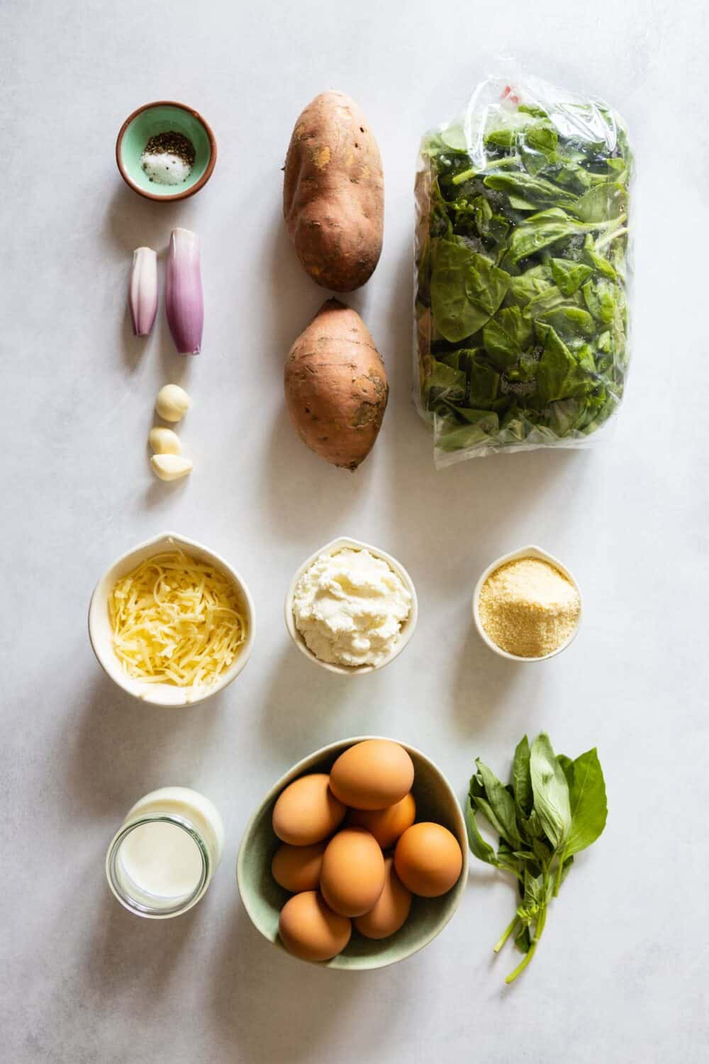 All ingredients for the crustless spinach quiche laid out on a kitchen counter.